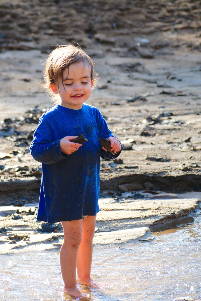 boy playing in the mud photographed by luxagraf