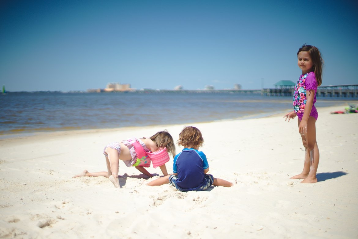 kids playing on the beach, ocean springs, ms photographed by luxagraf