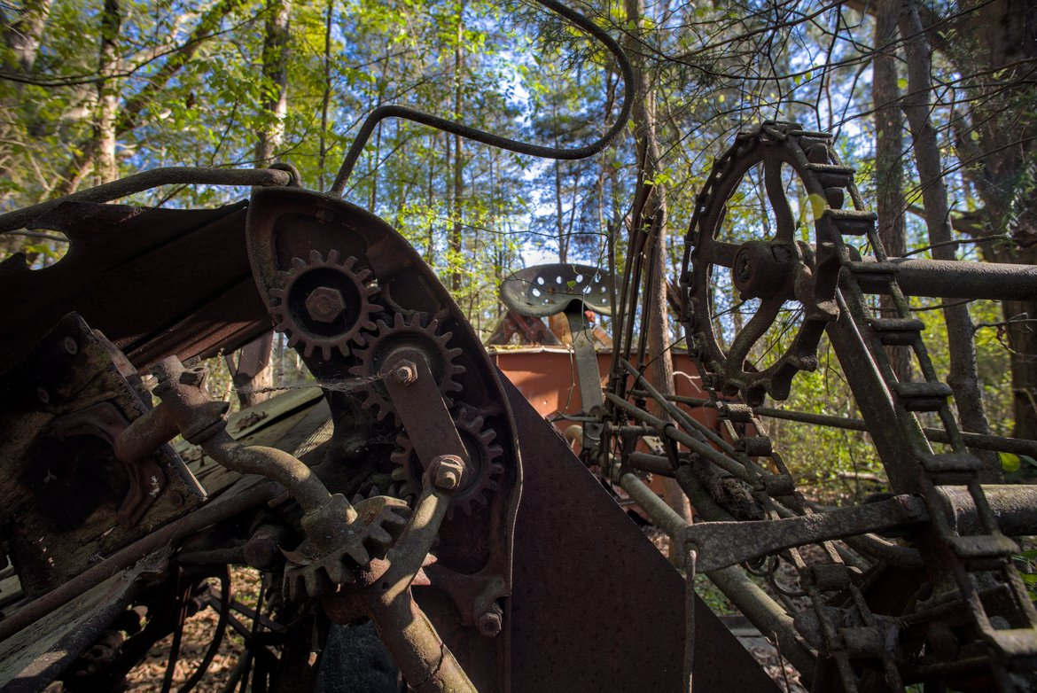rusted farm machinery in the woods photographed by luxagraf